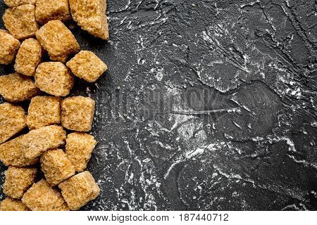 sugar in lumps for sweet food cooking on kitchen dark table background top view mock up