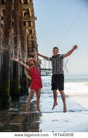 California teen boy and girl jumping for joy next to Ventura Pier.
