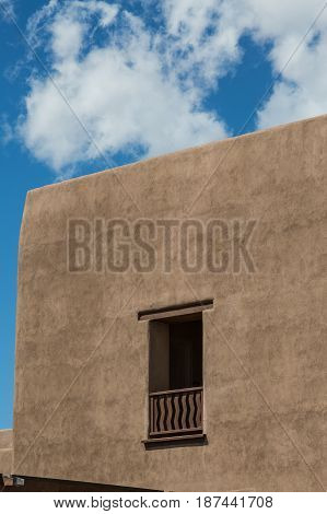 A brown adobe house against a blue sky