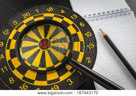 aiming target analysis concept with magnifying glass on dart board pencil and note paper.