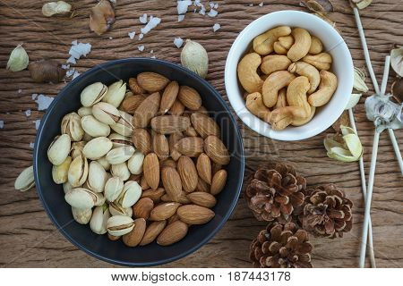 appetizer roasted healthy delicious salt pistachios cashew nuts and almonds food in black bowl on wooden table background.