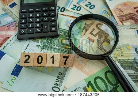 financial tax concept as magnifying glass on pile of euro banknotes calculator and number 2017 on wooden block.