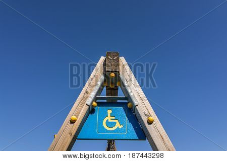 disabled sign and simbol on wooden swing pole playground with clear blue sky.