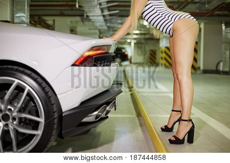 MOSCOW, RUSSIA - JUN 02, 2015: Young blonde woman (with model release) in striped bodysuit and high-heel shoes stands leaning hands on trunk of modern white Lamborghini at underground parking.
