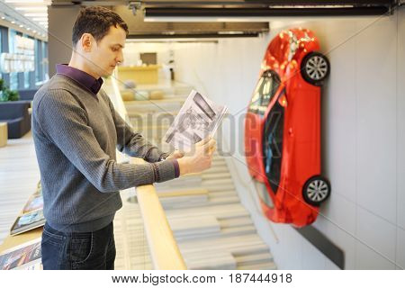 MOSCOW - APR 16, 2016: Red Hyundai Solaris on wall and man reads magazine (with model release) in Hyundai Motorstudio. Hyundai produces not only cars, but also its own collection of household items