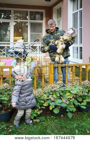 MOSCOW - OCT 25, 2016: Father with baby, girl (with MR) at terrace in summer residence of Mosdachtrest company, which manages summer houses fund, services and rents out-of-town property