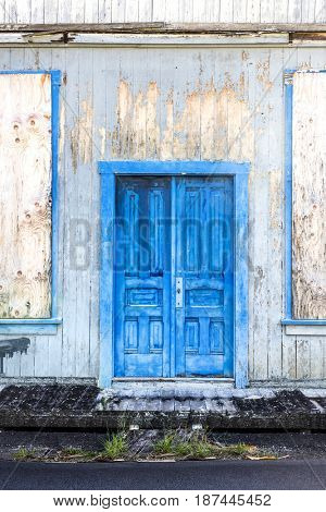 An old, antique blue door in the highlands of Hawaii show the damage that moisture has on wood.