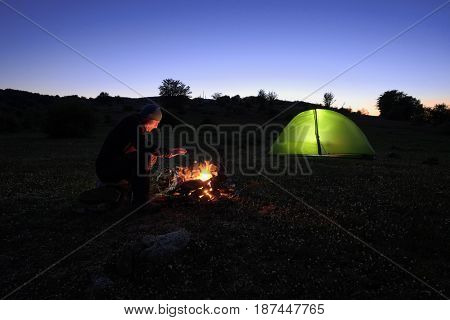 man heats on the campfire near the illuminated tent at dusk in Nebrodi Park, Sicily