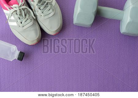 Fitness background with sport shoes gray dumbbells and water over violet yoga mat in gym Healty and lifestyle concept