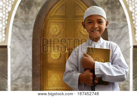 Asian muslim kid smile holding koran and beads