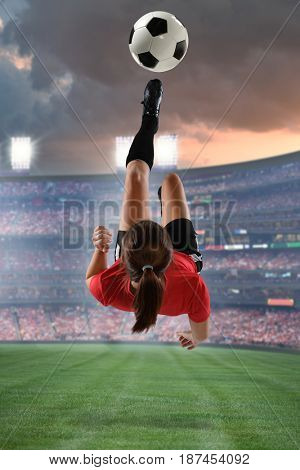 Young Female Soccer Player kicking the ball in mid-air inside stadium