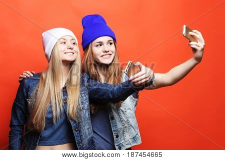 Two  girls friends in hipster outfit make selfie on a phone. Orange background.