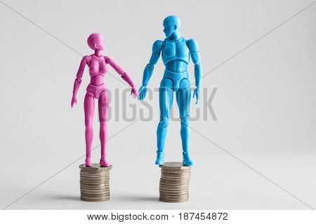 Male And Female Figurines Holding Hands Looking At Eachother, Standing On Top Of Equal Piles Of Coin