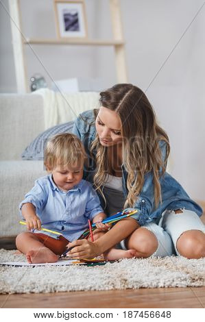 Mother and son paint the walls and floor. Children's creativity. Art for baby