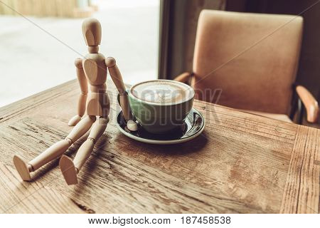 a wood man sitting and touch the hot mocha coffee or capuchino in the green cup on the wooden table