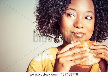 Black woman eating burger sandwich