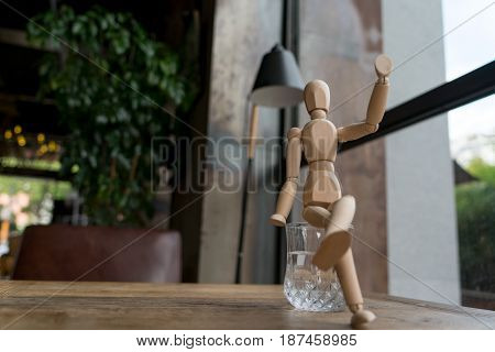 wood man is sitting on a glass of water while raise hand up