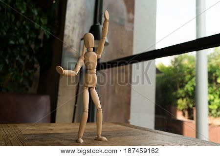 wood man is standing and raise the hand up