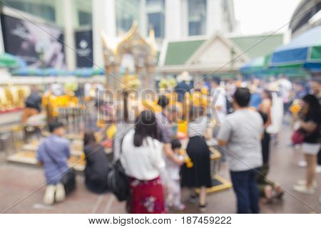 blurred background of worship people inside Erawan shrine at Ratchaprasong Junction in Bangkok Thailand.