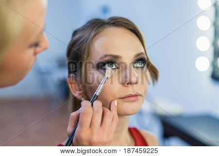 Make-up artist doing smoky eyes makeup to beautiful young girl in the studio Dressing room. The makeup artist has brush in hand