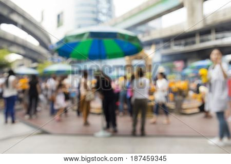 blurred background of unidentified people inside Erawan shrine at Ratchaprasong Junction in Bangkok Thailand.