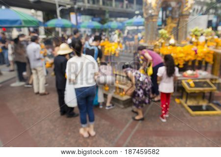 blurred background of worship people in Erawan shrine at Ratchaprasong Junction in Bangkok Thailand.