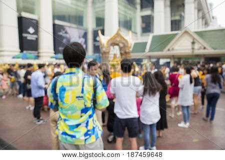 blurred background of unidentified tourist inside Erawan shrine at Ratchaprasong Junction in Bangkok Thailand.