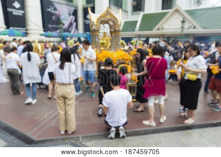blurred background of worship inside Erawan shrine at Ratchaprasong Junction in Bangkok Thailand.