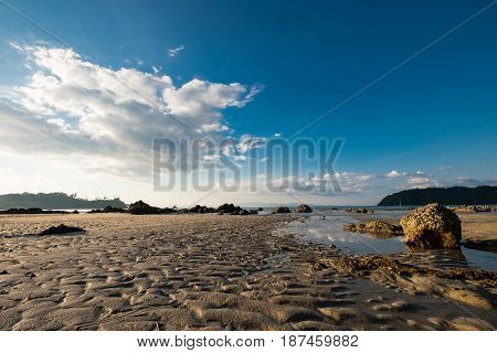Wet sand and the rock on the seashore when low tide in the evening.