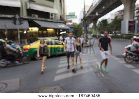 blurred scene of unidentified tourist walk across at Sukhumwit road in Bangkok Thailand