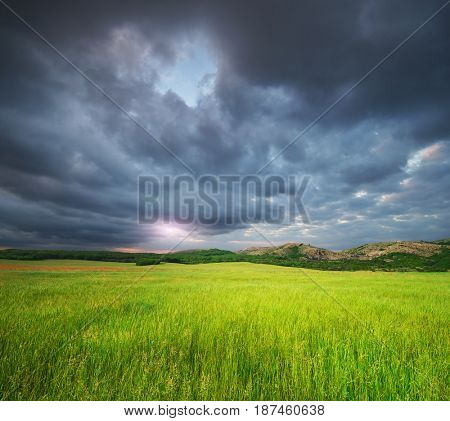 Green meadow in mountain and heavy rainy cloud. Composition of nature.