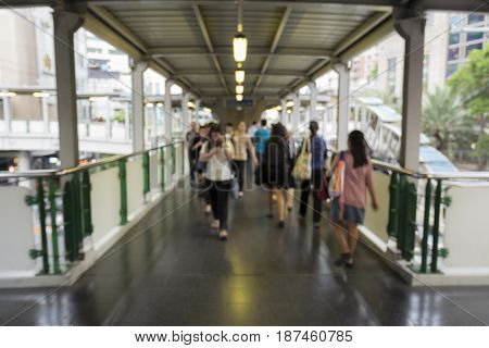 blurred background of unidentified people walk across at Asoke in Bangkok Thailand