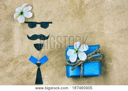Father's day greeting card applique face with glasses mustache and beard blue gift box with flower on crumpled paper