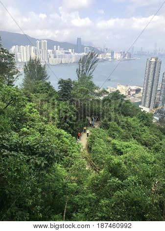 Hiking People In Mountain Footpath With Building