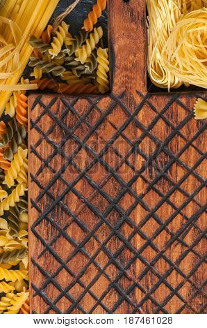 Assortment of raw types and shapes of italian pasta and wooden board on a black slate background. Close up. Top view and copy space.