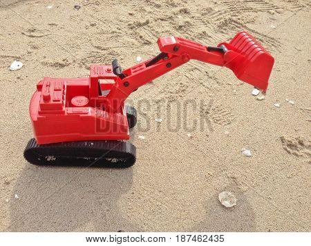 Children's toy red excavator car on sand,industrail symbols