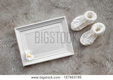 baby shower modern design with frame, clothes and toys on gray stone background top view mockup