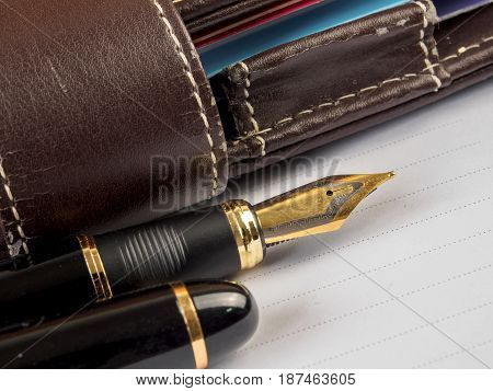 Fountain pen and notebook on white background