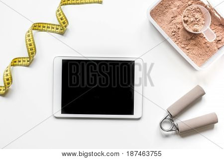 nutrition for workout with protein cocktail powder, tablet, measure tape and bars on white table background top view mockup