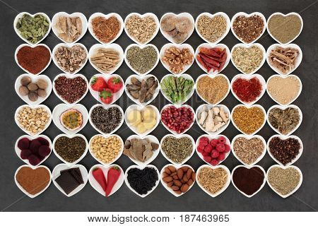 Aphrodisiac food sampler of foods to promote sexual health in heart shaped china bowls on slate background.