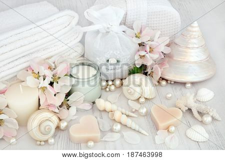 Natural spa beauty treatment cleansing products with apple blossom flowers, shells and pearls on distressed white wood background.