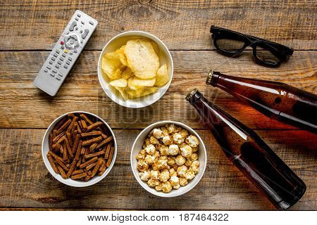 TV remote control, snacks, beer for whatchig film on wooden desk background top view