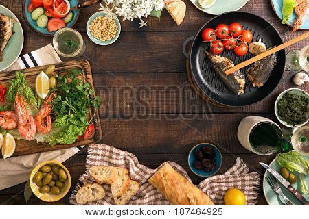 Frame of shrimp fish grilled salad different snacks and white wine on a rustic wooden table top view. Dinner table concept