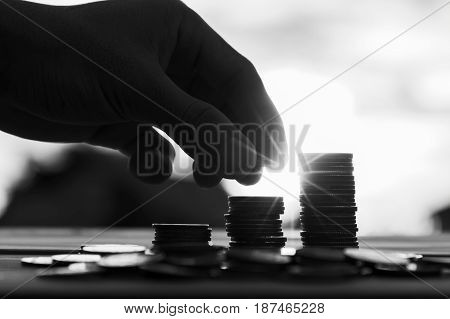 Saving money concept preset by Male hand putting money coin stack growing business. Close up of hand on sunset background Business Finance and Money concept Save money for prepare in the future