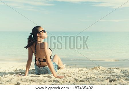 Young fashion woman relax on the beach. Happy island lifestyle. White sand blue cloudy sky and crystal sea of tropical beach. Vacation at Paradise. Ocean beach relax travel to Maldives islands.