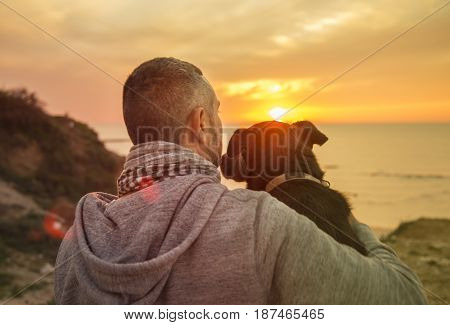 Man And His Faithful Dog Enjoying An Ocean Sunset