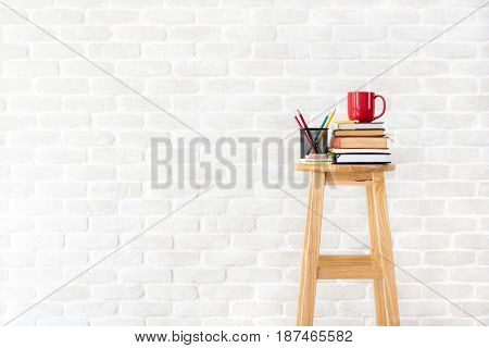 Booksstationery and coffee cup on wood stool in white brick wall background - idea creative and education concepts