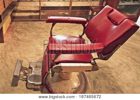 Old dark red chair in barber, retro tone