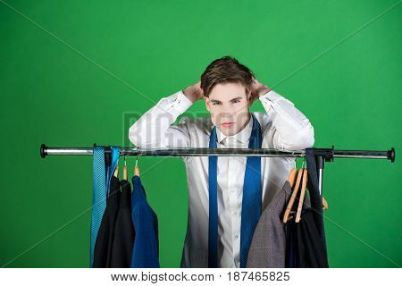 Shaved Man In Jacket And Tie Standing At Wardrobe Hanger