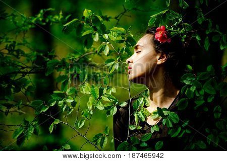 Woman With Flower In Hair In Green Tree Leaves